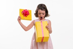 Child amazed at her present's content. Opened gift box with a big red ribbon on it. The top of the box in model's hands. White background, studio photo shoot.