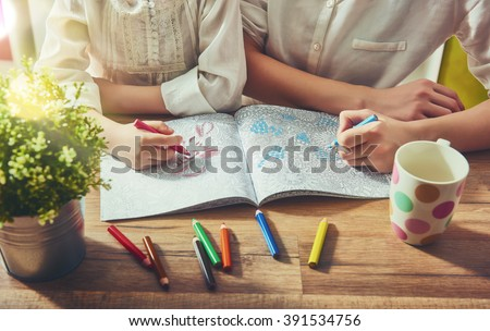 Child and adult  are painting a coloring book. New stress relieving trend. Concept mindfulness, relaxation.