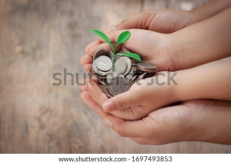 Child and adult hand holding money with green tree. Save money, family finance plan concept to buy house, economy, money in the future and education for thier child on wooden background