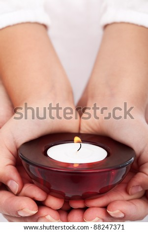 Child and adult hands holding candle - passing on traditions concept