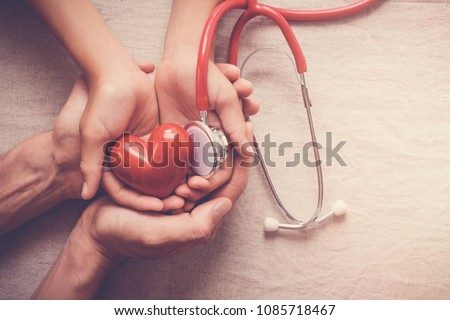 child and adult holding red heart with stethoscope, heart health,  health insurance concept