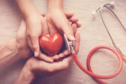 child and adult holding red heart with stethoscope, heart health,  health insurance concept, world health day, world hypertension day