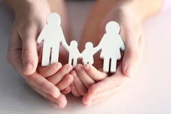 Child and adult person holding figure in shape of happy family, closeup. Adoption concept