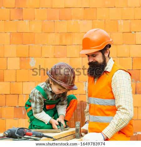 Child and father. Worker and professional builder with tools. Family builds a new house.