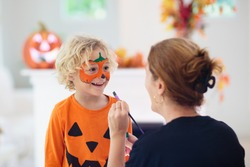 Child and mother in Halloween costume. Kids trick or treat. Face painting for party event. Little boy dressed as evil vampire with pumpkin lantern. Family celebration. Mom and son with candy.