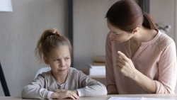 Child and parent conflict. Strict mother scolding lecturing stubborn preteen girl daughter sitting at desk reprimanding for bad behavior promise punishment. Angry mom rebuking idle kid for laziness