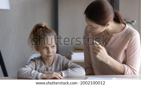 Child and parent conflict. Strict mother scolding lecturing stubborn preteen girl daughter sitting at desk reprimanding for bad behavior promise punishment. Angry mom rebuking idle kid for laziness ストックフォト ©