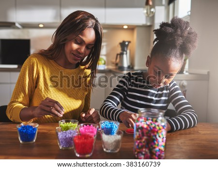 Child and parent sitting and creating color beaded crafts on wooden table in kitchen with various jars in front of them