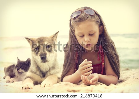 Child and puppy and kitten on a sandy beach