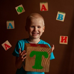 Child and Russian alphabet. Cubes with letters. The boy and the word alphabet on wooden blocks. Learning letters. A game with meaning. The alphabet game. RuBB alphabet for children. one child.