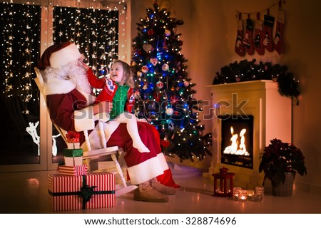 Stock Photo Child and Santa Claus in rocking chair at fireplace on Christmas eve. Family celebrating Xmas. Decorated living room with tree, gifts, fire place, candles. Winter evening at home for parents and kids.