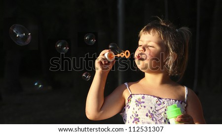 Child and soap bubbles Description: Little girl having fun with soap bubbles