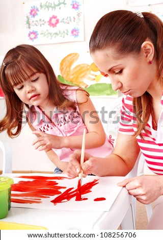 Child and teacher painting at easel in school.