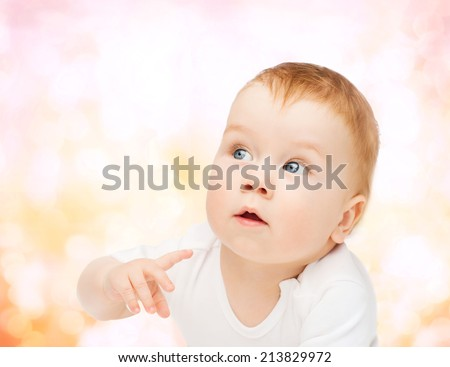 child and toddler concept - curious baby lying on floor and looking side