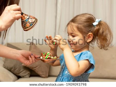 Child and traditional Ramadan candies.  Colorful sweet and baby girl.  Eid Mubarak. Kid hold plate full of sugar during Ramadan kareem (Turkish: Ramazan Bayrami).