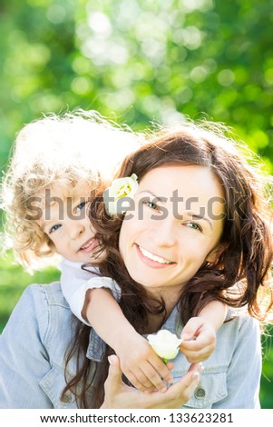 Child and young woman with flowers playing in spring park. Mothers day celebration concept