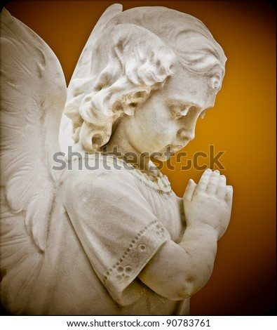 Child angel statue praying with a vintage look - stock photo