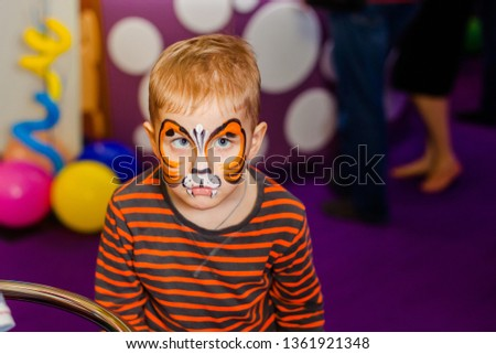 Child animator, artist's hand draws face painting to little boy. Child with funny face painting. Painter makes orange tiger at boy's face. Children holiday, event, birthday party, entertainment.