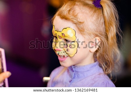 Child animator, artist's hand draws face painting to little girl. Child with funny face painting. Painter makes yellow leopard at girl's face. Children holiday, event, birthday party, entertainment.