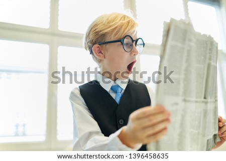 Child as a businessman reading the newspaper is amazed with open mouth