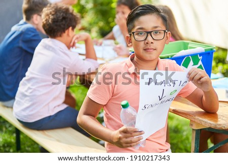 Child as a volunteer environmentalist in a recycling project at the holiday camp Stock foto ©