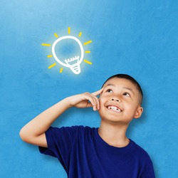 Child asian student thinking and looking up to light bulb on chalkboard. kid against blue concrete wall. Cute little boy has an new idea. Innovation technology and education concept