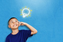 Child asian student thinking and looking up to light bulb on chalkboard. kid against blue concrete wall. Cute little boy has an new idea. Innovation technology and education concept. Copy space
