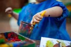 Child at nursery painting with a brush wearing a painting apron with paint all over it. Close up of the paints being mixed in a cup to make new colours for the picture they are making.