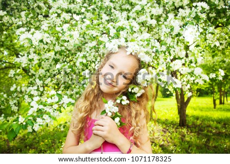 Child at spring. Happy girl outdoors. Blooming apple tree #1071178325