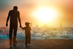 Child, baby holding an adult's hand. Father and son on a walk silhouette background. Children's day.