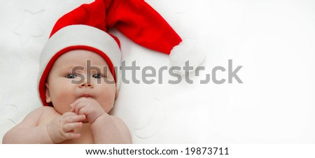 child baby in red Santa's hat lying on white blanket
