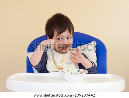 Child, baby or toddler sitting in a high chair eating with spoon from a bowl.