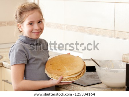 Child bakes pancakes in the kitchen. Girl cooking breakfast