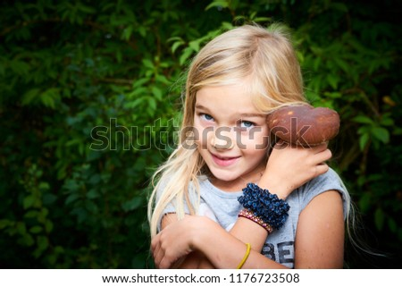 Child blong girl posing in forest and holding fresh picked mushroom (boletus). Selective focus #1176723508