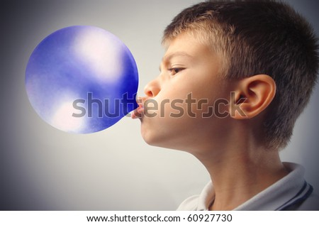 Child blowing a blue bubble gum