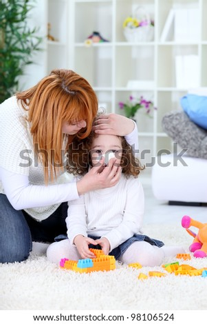 Child blowing nose, mothers help with handkerchief