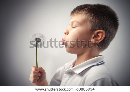 Child blowing on a dandelion