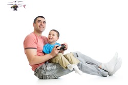Child boy and dad playing with RC helicopter toy