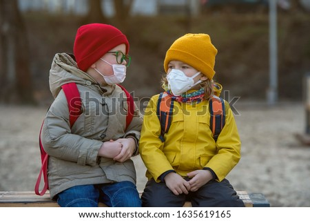 Child boy and girl playing outdoors with face mask protection. School boy breathing through medical mask. Children from kindergarten playing on playground.