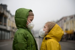Child boy and girl walking outdoors with face mask protection. School boy breathing through medical mask because of smog and air pollution. Children in bright yellow rain coat.