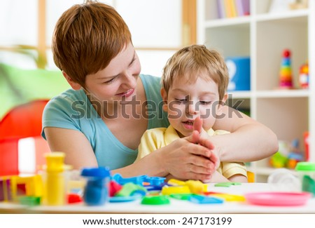 child boy and woman play colorful clay toy at playroom