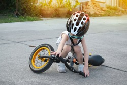 child boy attempt standing of balance bike from falling down