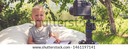 Child boy blogging for a camera on nature, the idea of youth hobbies, freelancing, earning a hobby