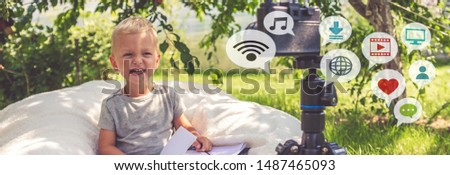 Child boy blogging for a camera on nature, the idea of youth hobbies, freelancing, earning a hobby alpha generation #1487465093