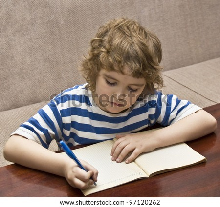 Child (boy eight years, European) writing in notebook.