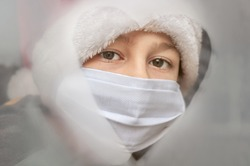 Child boy girl a santa claus hat, protective mask looks through the drawn a heart in the misted window. Christmas holidays 2021. Covid-19, Coronavirus. Waiting. Winter. Isolation at home. Hospital