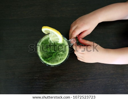 Child (boy) hands holding healthy Spinach green vegetable smoothie as a healthy summer drink with ingredients on wooden table. Healthy concept. Top view. Space for text. - Shutterstock ID 1072523723