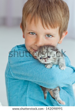 child boy holding cat kitten isolated