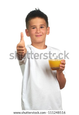 Child boy holds a glass with orange juice and shows yes