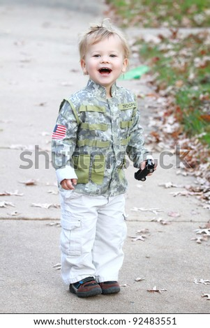 Child, boy in a soldier outfit laughing outdoors